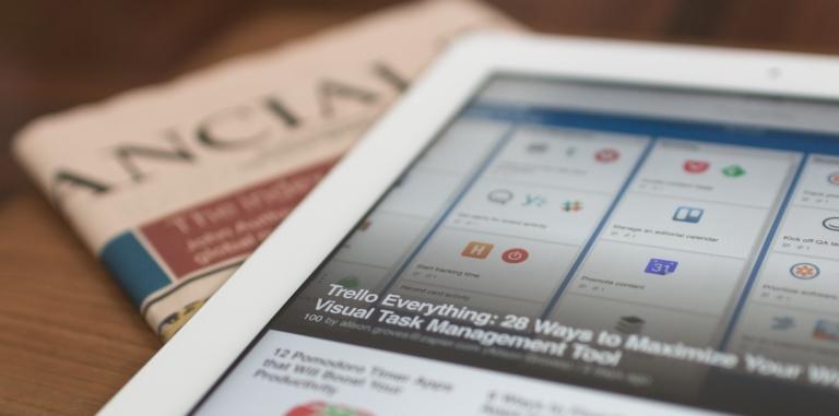 tablette tactile posée sur une table avec un article d'affiché sur l'écran