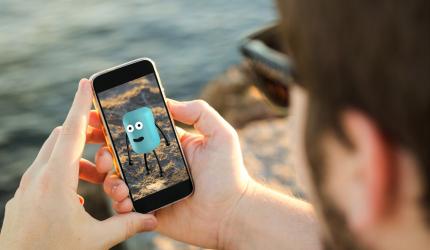 une personne qui est sur son téléphone et qui regarde une animation en réalité augmentée