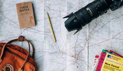 un appareil photo reflex, un carnet, un crayon, un sac à dos et des livres de voyage sont posés sur une carte routière