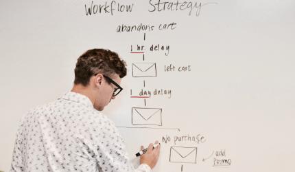 une personne écrit sur un tableau blanc des information concernant un workflow d'e-mails