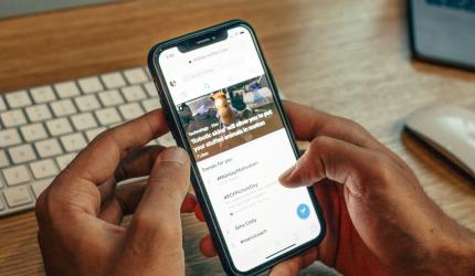 une personne qui tient son téléphone portable dans les mains. Le téléphone affiche la page d'une application mobile
