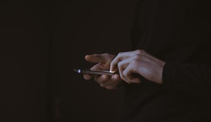personne qui tient un téléphone portable dans ses mains