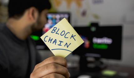 un homme tient un post-it avec écrit Blockchain dessus