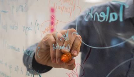 une personne qui écrit sur un tableau transparent