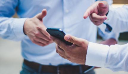 deux personnes dont l'une qui montre quelque chose sur un téléphone portable