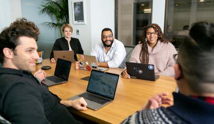 personnes autour d'une table de réunion en train de converser avec le sourire