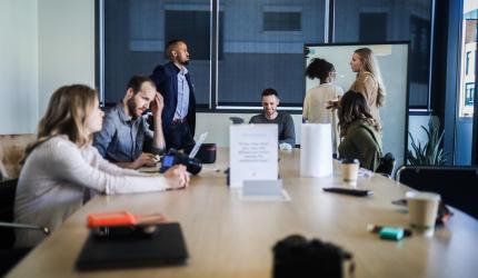 personnes assises autour d'une table dans une salle de réunion