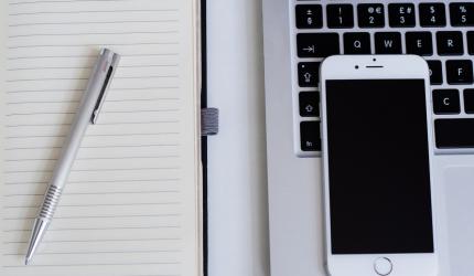 bloc-note avec stylo positionné à côté d'un Iphone blanc