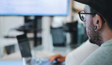 on voit un homme de profil avec un écran d'ordinateur à proximité de lui