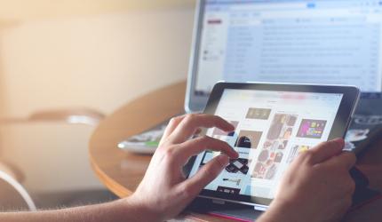 vue sur l'écran d'une tablette tactile avec la main d'une personne qui touche l'écran pour agrandir une image