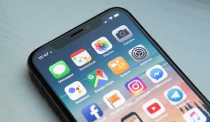 Téléphone portable Apple posé sur une table avec l'écran d'accueil allumé