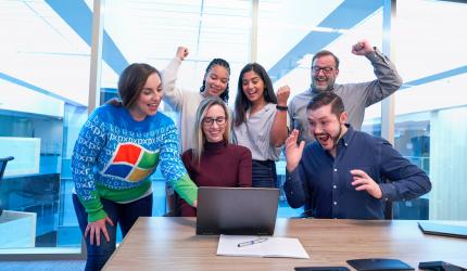 une équipe de 6 personnes qui regardent un écran avec joie